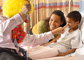 Pediatrician with Balloons and Clown Costume Making Young Patient Laugh