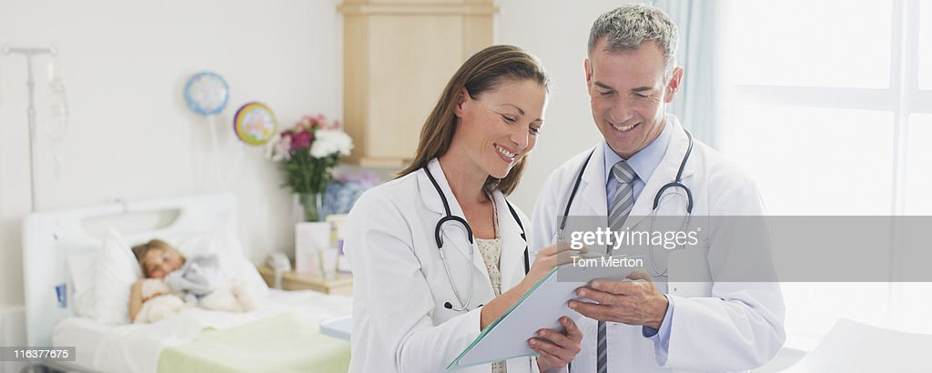 Pediatricians reviewing patients medical record in hospital : Stock Photo