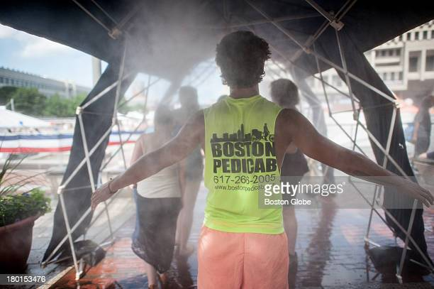 A pedicab driver cooled off at a vapor shower during another day of 90 degree heat in Boston