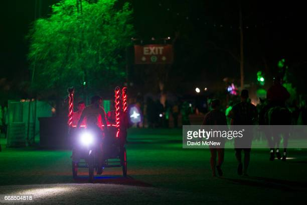 Pedicab driver gives people a lift as music fans camp out at the Empire Polo Club on the eve of the 2017 Coachella Valley Music And Arts Festival on...