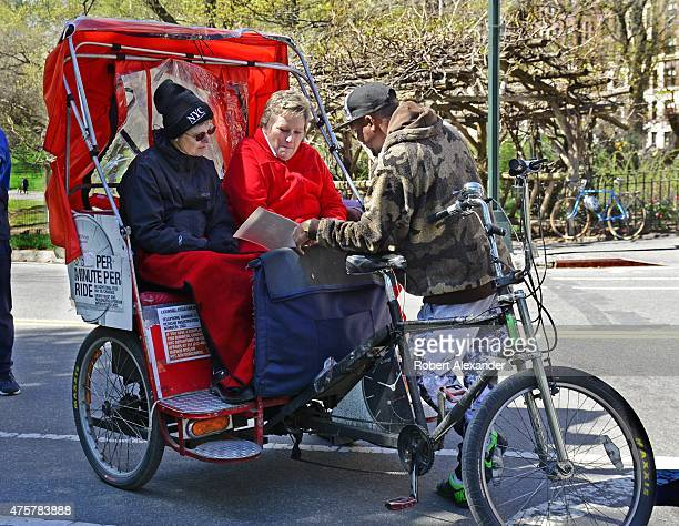 A pedicab driver talks with his tourist passengers before taking the New York City visitors on a tour of Manhattan's Central Park area