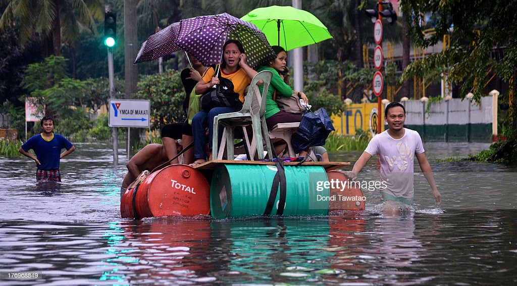 Pedicabs and makeshift rafts ferry office workers and pedestrians through floodwaters that submerged parts of the financial district of Makati on August 20, 2013 in Makati City south of Manila, Philippines. Schools, government offices and financial markets suspended classes and work except for rescues and disaster response as torrential rains enhanced by the southwestern monsoon inundated much of the metropolis for a second day. Major roads were impassable as floodwaters reached waist or neck deep in some areas forcing thousands of residents living near waterways and creeks to evacuate their homes and seek shelter. At least seven fatalities were recorded with thousands more still needing to be rescued.