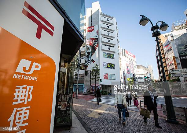 Pedrestians walk by a Japan Post Co branch in downtown Tokyo on November 4 2015 in Tokyo Japan Shares in Japan Post with its banking and insurance...