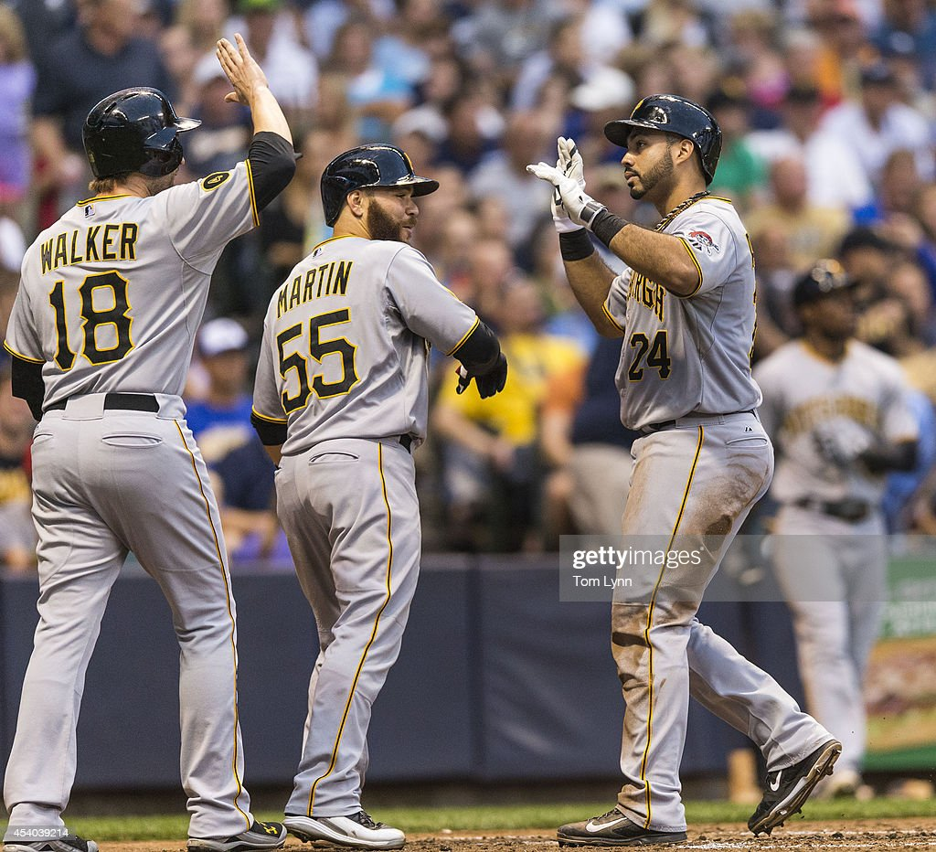 Pedro Alvarez #24 of the Pittsburg Pirates celebrates with teammates Neil Walker #18 and <a gi-track='captionPersonalityLinkClicked' href=/galleries/search?phrase=Russell+Martin+-+Baseball+Player&family=editorial&specificpeople=13764024 ng-click='$event.stopPropagation()'>Russell Martin</a> #55 after hitting a three-run homer off of Wiley Peralta #38 of the Milwaukee Brewers at Miller Park on August 23, 2014 in Milwaukee, Wisconsin.