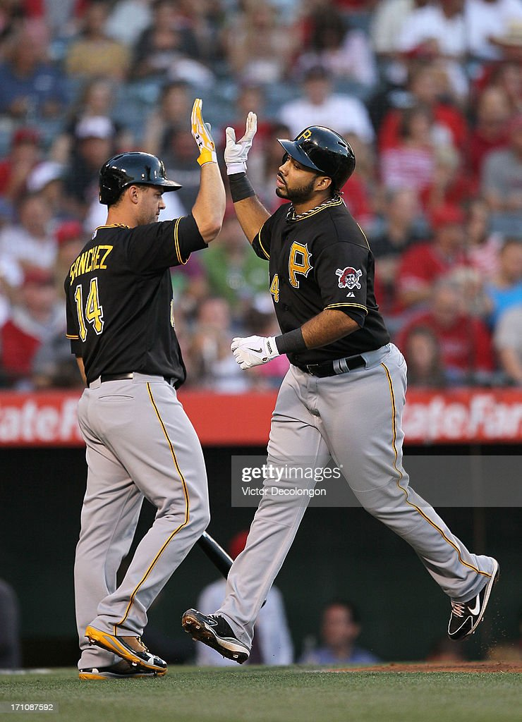 Pedro Alvarez #24 of the Pittsburgh Pirates celebrates with teammate Gaby Sanchez #14 at home plate after hitting a solo home run in the second inning during the MLB game against the Los Angeles Angels of Anaheim at Angel Stadium of Anaheim on June 21, 2013 in Anaheim, California.