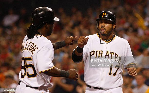 Pedro Alvarez of the Pittsburgh Pirates congratulates teammate Lastings Milledge after they scored in the second inning against the Cincinnati Reds...