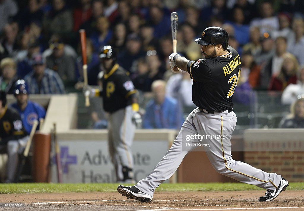 Pedro Alvarez #24 of the Pittsburgh Pirates follows through on an RBI ground-rule double scoring Marlon Byrd #2 during the second inning against the Chicago Cubs at Wrigley Field on September 24, 2013 in Chicago, Illinois.