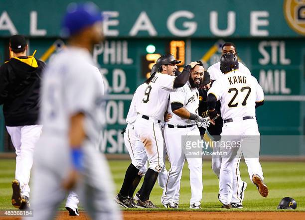 Pedro Alvarez of the Pittsburgh Pirates is congratulated by teammates including Francisco Cervelli and Jung Ho Kang following his walk off...