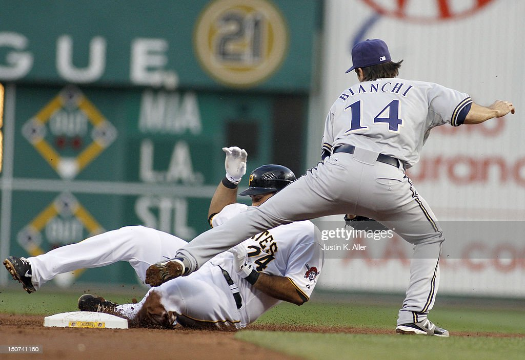 Pedro Alvarez #24 of the Pittsburgh Pirates slides in safe against Jeff Bianchi #14 of the Milwaukee Brewers during the game on August 25, 2012 at PNC Park in Pittsburgh, Pennsylvania.