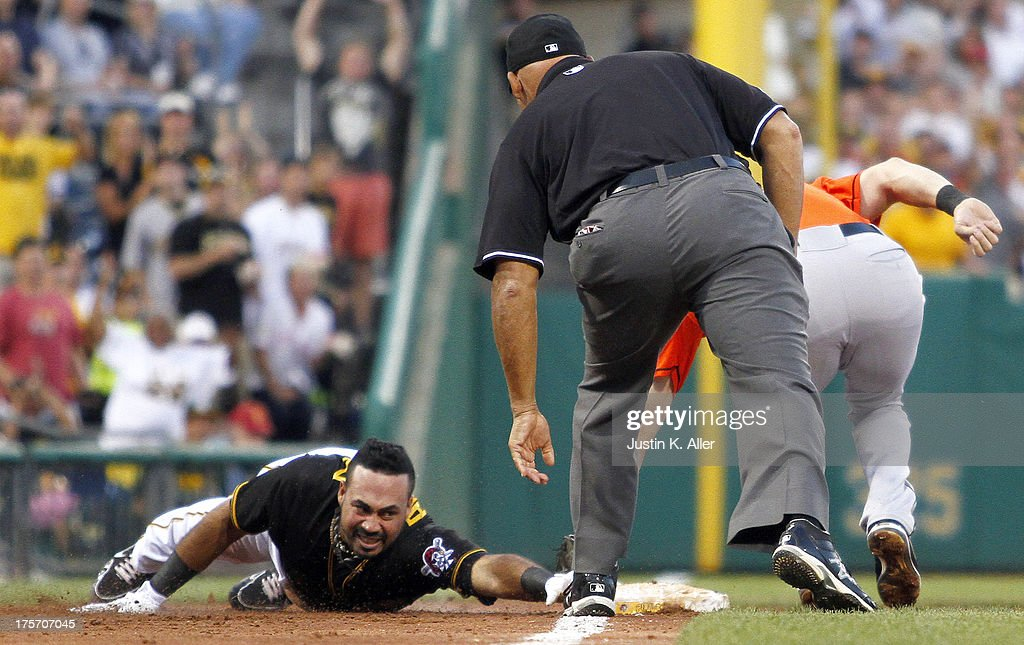 Pedro Alvarez #24 of the Pittsburgh Pirates slides in safe for a triple in the third inning against Ed Lucas #59 of the Miami Marlins during the game on August 6, 2013 at PNC Park in Pittsburgh, Pennsylvania.