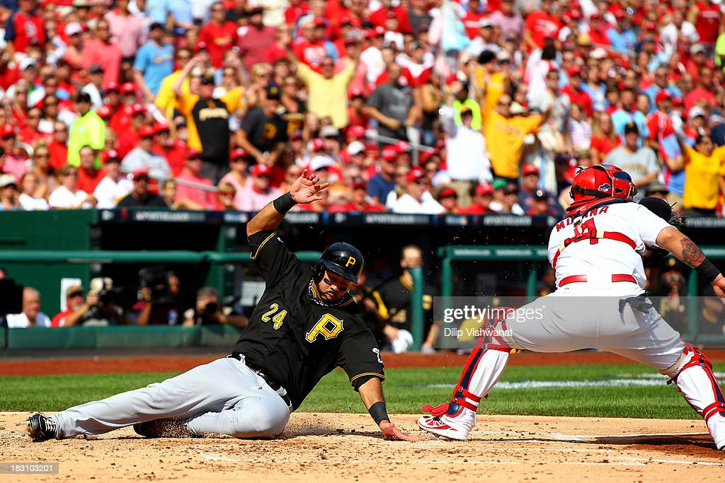 Pedro Alvarez #24 of the Pittsburgh Pirates slides safely to score a run in the second inning before catcher Yadier Molina #4 of the St. Louis Cardinals gets the ball during Game Two of the National League Division Series at Busch Stadium on October 4, 2013 in St Louis, Missouri.