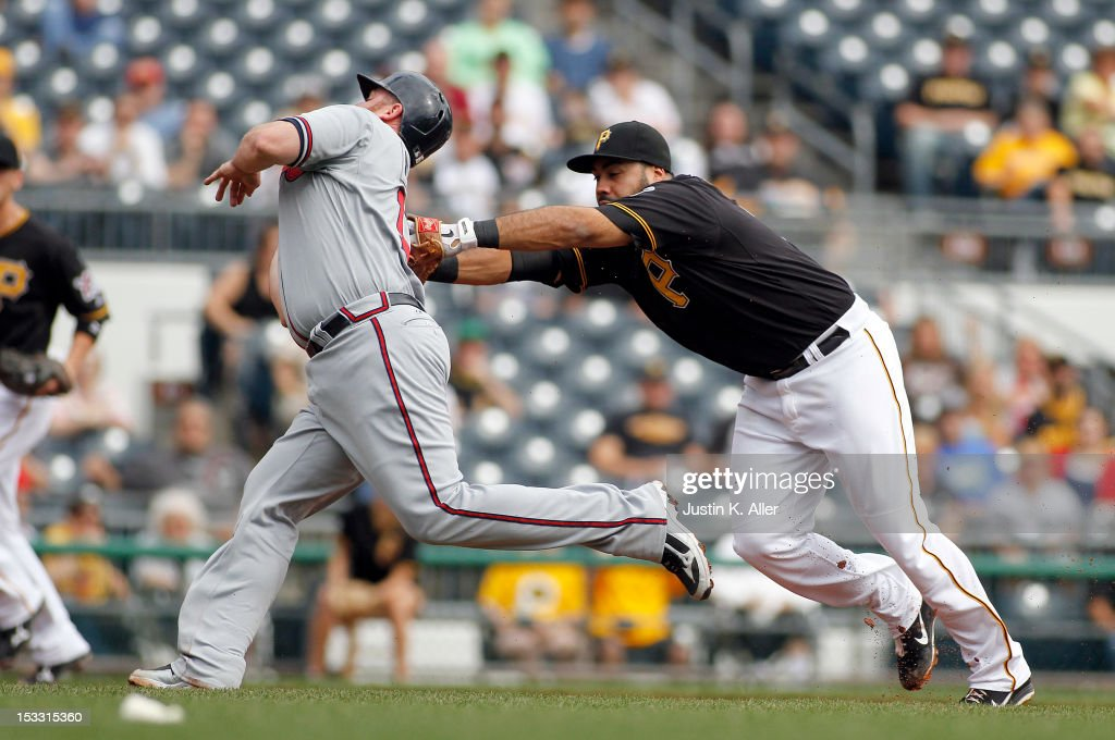 Pedro Alvarez #24 of the Pittsburgh Pirates tags <a gi-track='captionPersonalityLinkClicked' href=/galleries/search?phrase=Brian+McCann+-+Honkballer&family=editorial&specificpeople=593065 ng-click='$event.stopPropagation()'>Brian McCann</a> #16 of the Atlanta Braves during the game on October 3, 2012 at PNC Park in Pittsburgh, Pennsylvania.