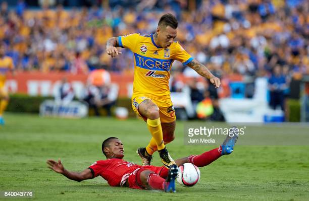 Pedro Aquino of Lobos BUAP slides for the ball as Eduardo Vargas of Tigres tries to driibble during the seventh round match between Tigres UANL and...