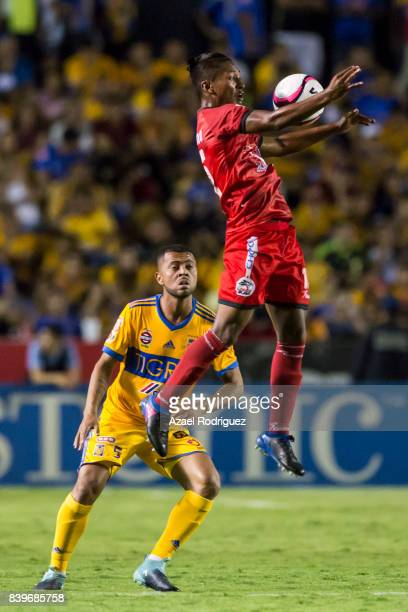Pedro Aquino of Lobos controls the ball while is observed by Rafael de Souza of Tigres during the seventh round match between Tigres UANL and Lobos...