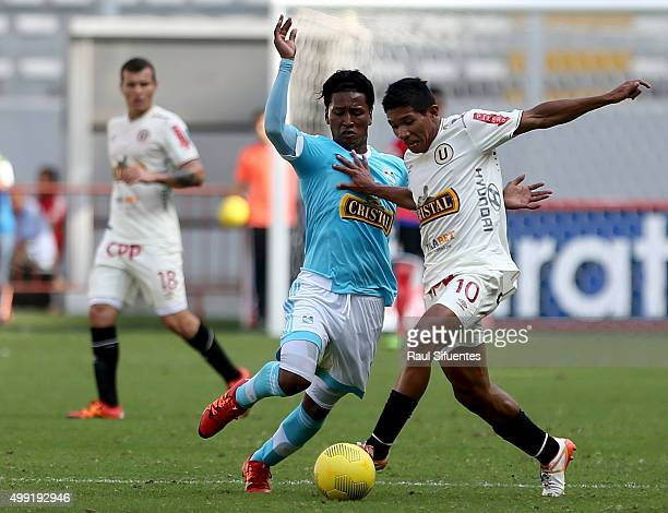 Pedro Aquino of Sporting Cristal fightss for the ball with Edison Flores of Universitario during a match between Sporting Cristal and Universitario...