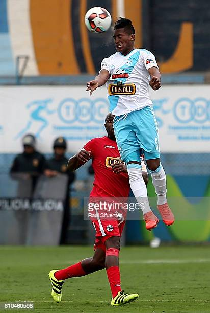 Pedro Aquino of Sporting Cristal heads the ball over Luis Tejada of Juan Aurich during a match between Sporting Cristal and Juan Aurich as part of...