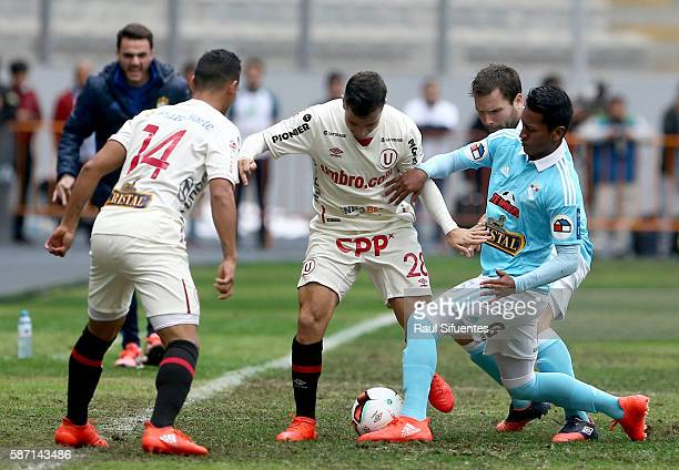 Pedro Aquino of Sporting Cristal struggles for the ball with Diego Guastavino of Universitario during a match between Universitario and Sporting...