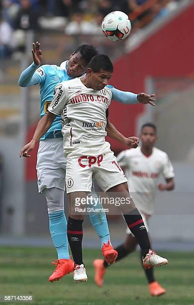 Pedro Aquino of Sporting Cristal struggles for the ball with Edison Flores of Universitario during a match between Universitario and Sporting Cristal...