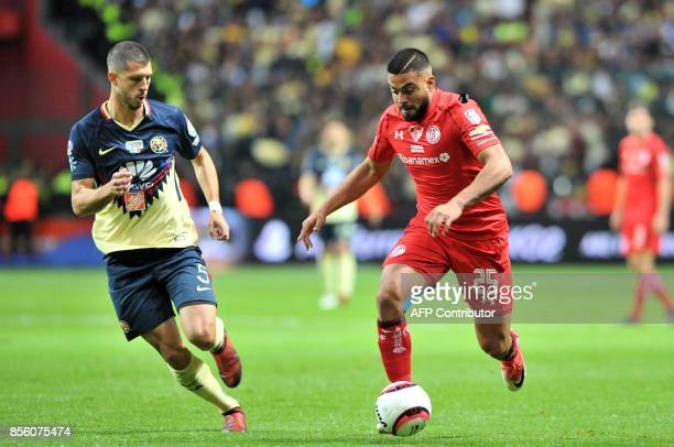 Pedro Canelo of Toluca is marked by Guido Rodriguez of America during their Mexican Apertura football tournament match at the Nemesio Diez stadium in...