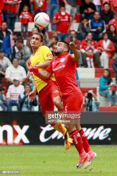 Pedro Canelo of Toluca jumps for a header with Emanuel Loeschbor of Morelia during their Mexican Apertura tournament football match at the Nemesio...