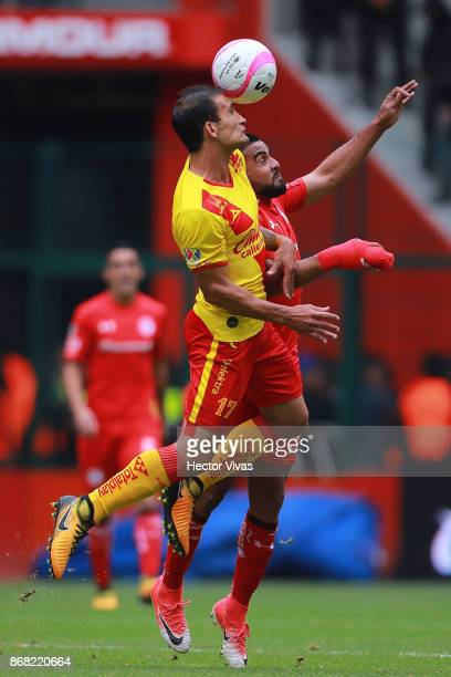 Pedro Canelo of Toluca struggles for the ball with Emanuel Loeschbor of Morelia during the 15th round match between Toluca and Morelia as part of the...