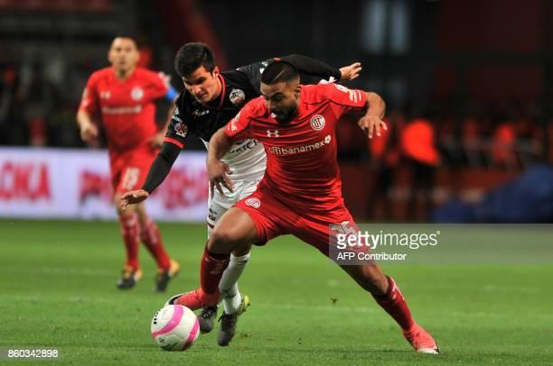 Pedro Canelo of Toluca vies for the ball with Eduardo Tercero of Lobos Buap during their Mexican Apertura tournament football match at the Nemesio...
