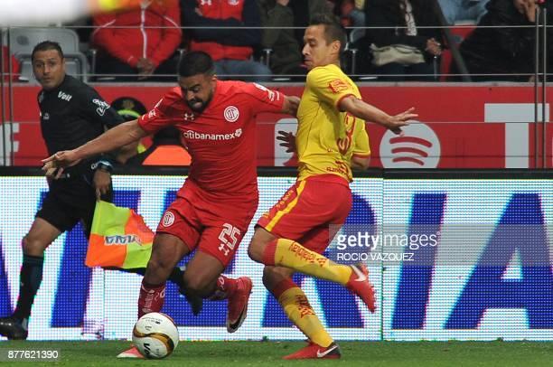 Pedro Canelo of Toluca vies for the ball with Gerardo Rodriguez of Morelia during their quarter final Mexican Apertura tournament football match at...
