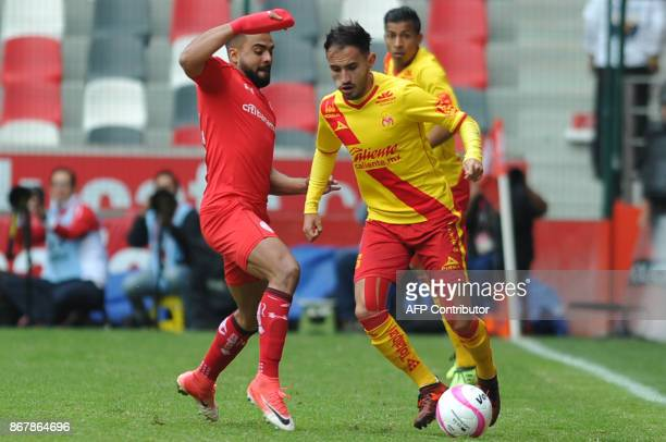 Pedro Canelo of Toluca vies for the ball with Morelia's Carlos Guzman during their Mexican Apertura tournament football match at the Nemesio Diez...