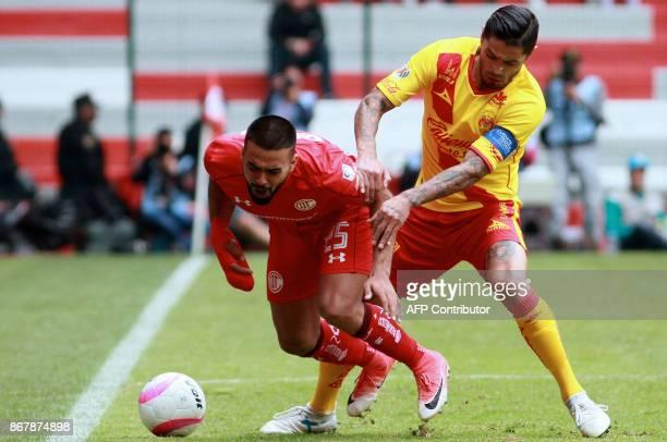 Pedro Canelo of Toluca vies for the ball with Rodrigo Millar of Morelia during their Mexican Apertura tournament football match at the Nemesio Diez...