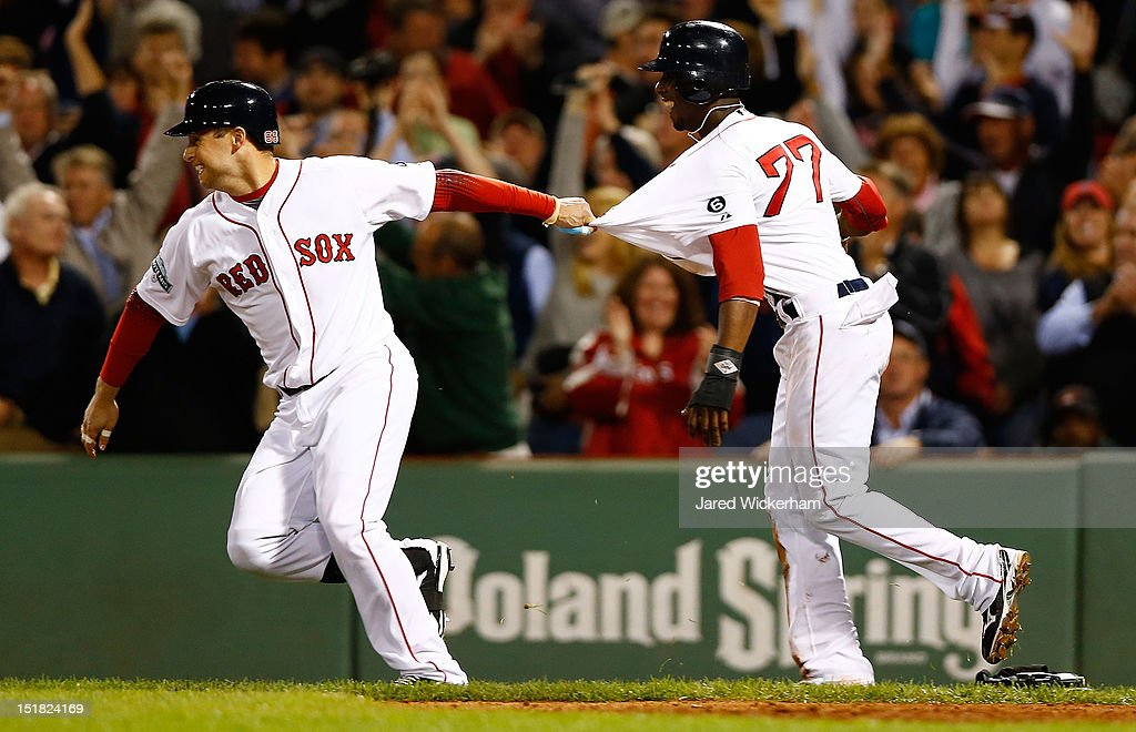 Pedro Ciriaco #77 of the Boston Red Sox celebrates with teammate Daniel Nava #66 following their walk-off win against the New York Yankees in the bottom of the ninth inning during the game on September 11, 2012 at Fenway Park in Boston, Massachusetts.