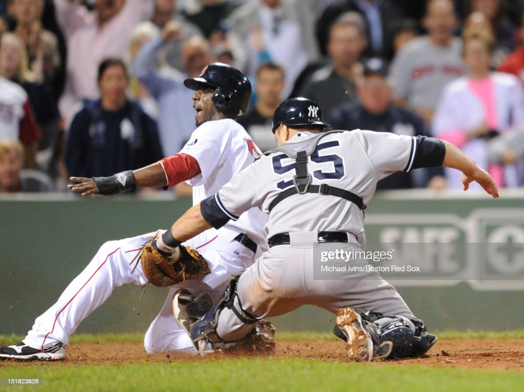 Pedro Ciriaco #77 of the Boston Red Sox slides safely ahead of the tag by Russell Martin #55 of the New York Yankees to score the game winning run in the ninth inning on September 11, 2012 at Fenway Park in Boston, Massachusetts.