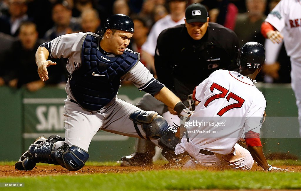 Pedro Ciriaco #77 of the Boston Red Sox slides safely into home plate to score in front ot Russell Martin #55 of the New York Yankees in the bottom of the ninth inning to win the game during the game on September 11, 2012 at Fenway Park in Boston, Massachusetts.