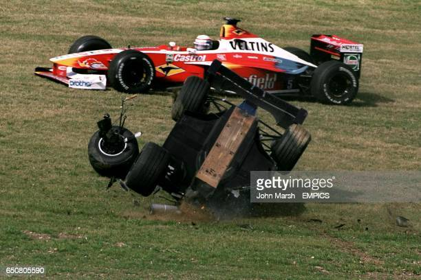 Pedro Diniz rolls his car after his crash with Alexander Wurz as Alex Zanardi drives past