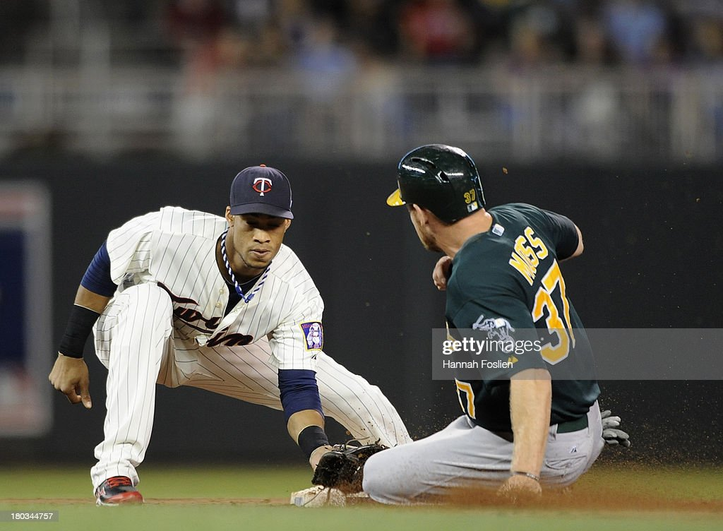 Pedro Florimon #25 of the Minnesota Twins catches <a gi-track='captionPersonalityLinkClicked' href=/galleries/search?phrase=Brandon+Moss&family=editorial&specificpeople=702783 ng-click='$event.stopPropagation()'>Brandon Moss</a> #37 of the Oakland Athletics stealing second base during the third inning of the game on September 11, 2013 at Target Field in Minneapolis, Minnesota.
