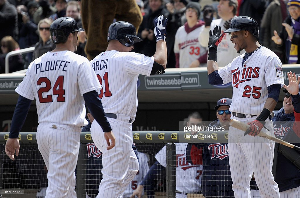Pedro Florimon #25 of the Minnesota Twins congratulates teammates <a gi-track='captionPersonalityLinkClicked' href=/galleries/search?phrase=Trevor+Plouffe&family=editorial&specificpeople=5722348 ng-click='$event.stopPropagation()'>Trevor Plouffe</a> #24 and <a gi-track='captionPersonalityLinkClicked' href=/galleries/search?phrase=Oswaldo+Arcia&family=editorial&specificpeople=8948415 ng-click='$event.stopPropagation()'>Oswaldo Arcia</a> #31 on scoring on a three=run home run by Arcia against the Miami Marlins during the fourth inning of the first game of a doubleheader on April 23, 2013 at Target Field in Minneapolis, Minnesota.