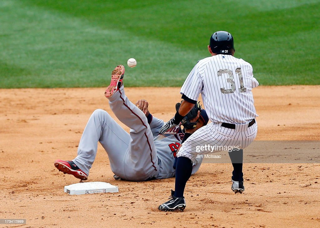 Pedro Florimon #25 of the Minnesota Twins loses his balance after forcing out <a gi-track='captionPersonalityLinkClicked' href=/galleries/search?phrase=Ichiro+Suzuki&family=editorial&specificpeople=201556 ng-click='$event.stopPropagation()'>Ichiro Suzuki</a> #31 of the New York Yankees at second base during the eighth inning at Yankee Stadium on July 13, 2013 in the Bronx borough of New York City.