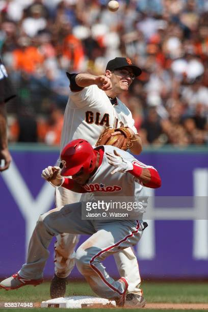 Pedro Florimon of the Philadelphia Phillies breaks up a double play attempt by Kelby Tomlinson of the San Francisco Giants during the fifth inning at...