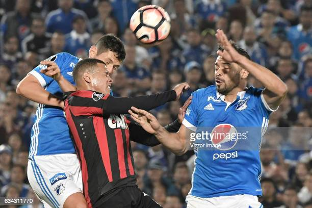 Pedro Franco and Andres Cadavid of Millonarios jump for a header with Sidcley of Atletico Paranaense during a match between Millonarios and Atletico...
