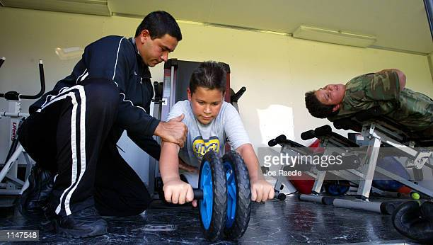 Pedro Hernandez who runs the Mobile Gym For Kids shows Mike Echevarria how to properly do an abdominal exercise July 22 2002 in Miami Florida Nearly...