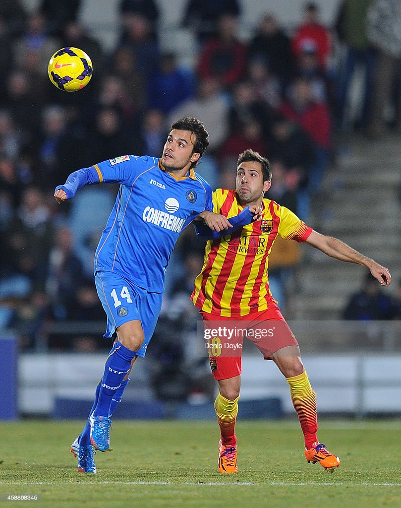 Pedro Leon (L) of Getafe CF battles for the ball against Jordi Alba of FC Barcelona during the La Liga match between Getafe CF and FC Barcelona at Coliseum Alfonso Perez on December 22, 2013 in Getafe, Spain.