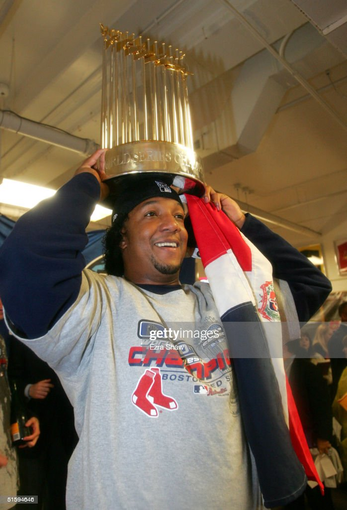 Pedro Martinez of the Boston Red Sox celebrates with the Championship trophy after defeating the St Louis Cardinals 30 to win game four of the World...