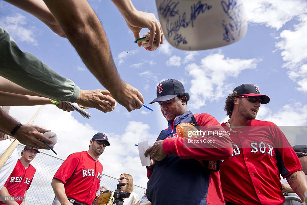 Pedro Martinez, special assistant to the general manager of the Boston Red Sox, signs his autograph for fans as catchers, left to right, Matt Spring, Jason Varitek, and Jarrod Saltalamacchia walk by during spring training at JetBlue Park on Tuesday, Feb. 19, 2013.