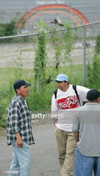 Pedro Mendoza left an immigrant from Durango Mexico talks with other day laborers as they wait to be picked up for work in Nashville Tennessee on...