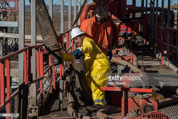 Pedro Michel and Julio Perez floor hands connect large tubing to be used to vacuum remaining sediments in a storage tank on a Raven Oil Drilling rig...