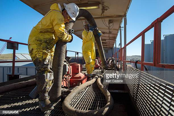 Pedro Michel left and Julio Perez right both floor hands work at installing a tube to vacuum out remaining sediment in a storage tank on a Raven Oil...
