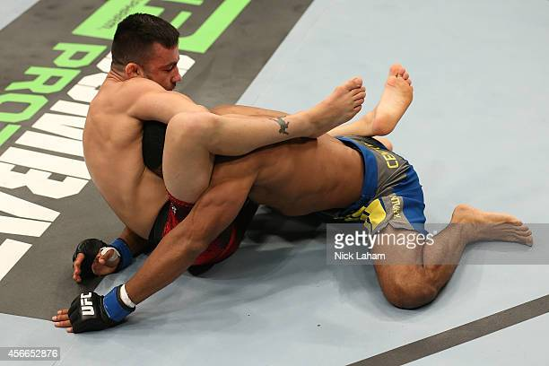 Pedro Munhoz of Brazil locks in a guillotine submission against Jerrod Sanders in their bantamweight bout at the Scotiabank Centre on October 4 2014...