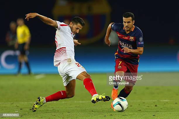 Pedro of Barcelona evades a tackle from Vitolo of Sevilla during the UEFA Super Cup between Barcelona and Sevilla FC at Dinamo Arena on August 11...
