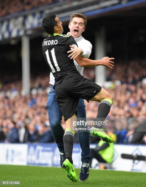 Pedro of Chelsea celebrates scoring his sides first goal with a Chelsea fan who invaded the pitch during the Premier League match between Everton and...