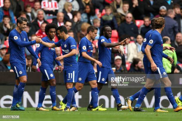 Pedro of Chelsea celebrates scoring his side's second goal with his team mates during the Premier League match between Stoke City and Chelsea at...