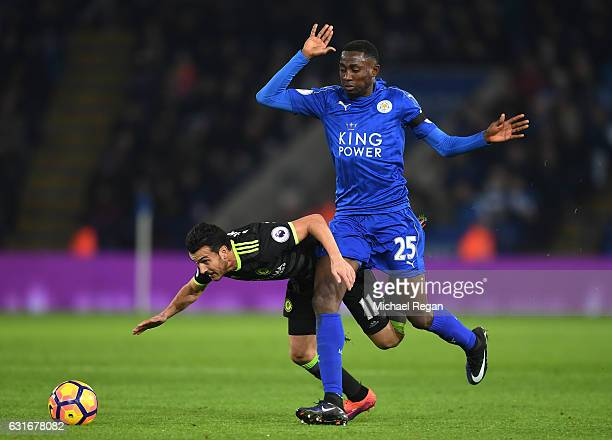 Pedro of Chelsea goes down under the challenge from Wilfred Ndidi of Leicester City during the Premier League match between Leicester City and...